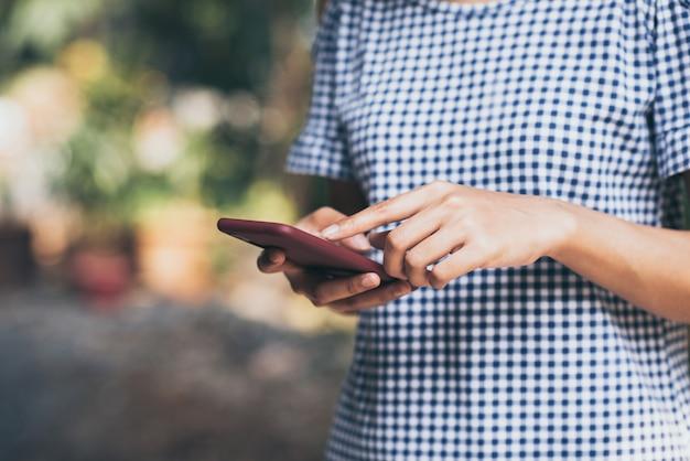 Giovane donna asiatica che usando la natura all'aperto del telefono cellulare