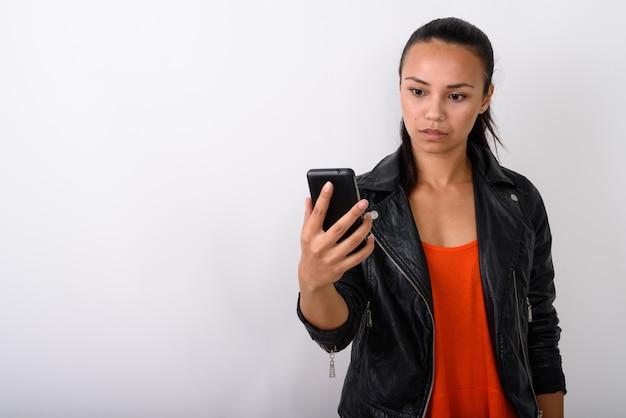 Giovane donna asiatica utilizzando il telefono cellulare mentre indossa la giacca di pelle contro uno spazio bianco