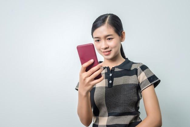 Giovane donna asiatica che per mezzo del telefono, sistema di riconoscimento facciale, concetti di biometria.