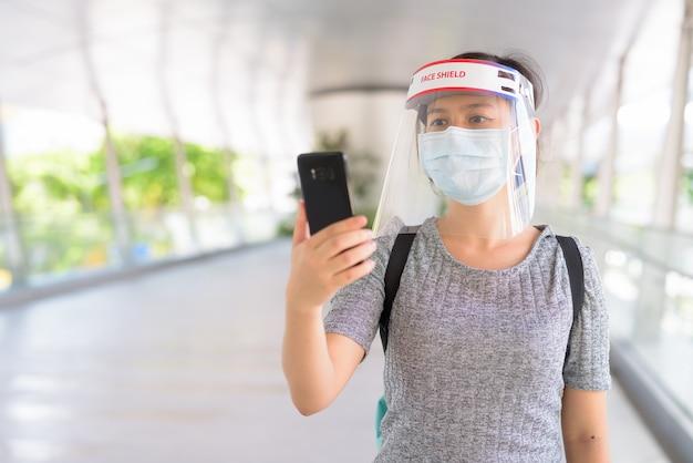 Giovane donna asiatica che utilizza il telefono con maschera e schermo facciale per la protezione dallo scoppio del virus corona in città