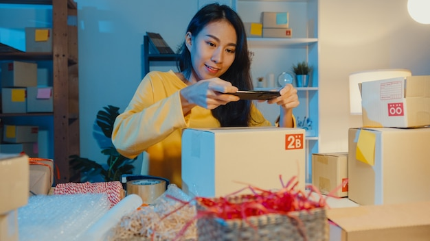 Giovane donna asiatica che utilizza smartphone che cattura l'immagine del codice a barre sul prodotto del pacco per la consegna di spedizione al cliente