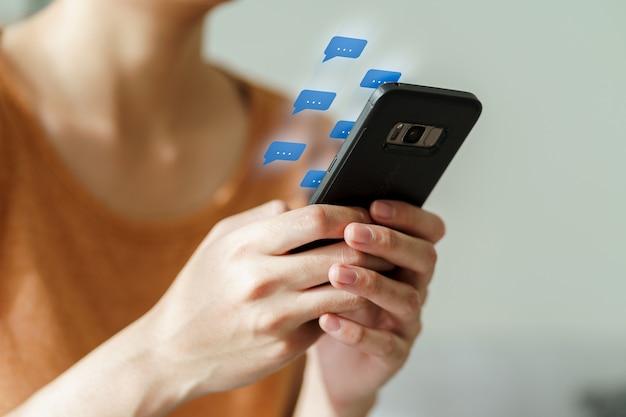 Giovane donna asiatica che utilizza la digitazione dello smartphone, conversazione in chat. social network, concetto di tecnologia