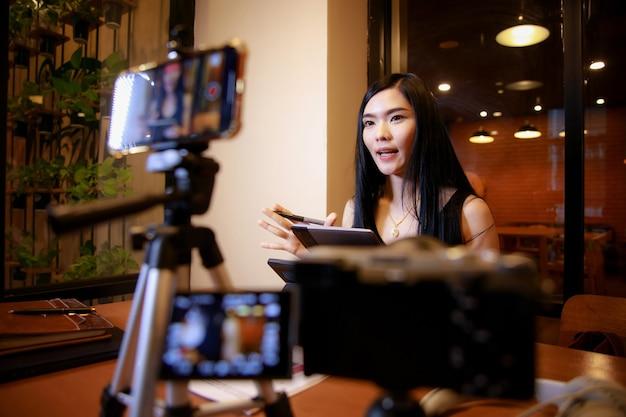 Giovane donna asiatica vlogger che registra contenuti video per il canale onlinefemmina guardando la fotocamera e parlando durante le riprese videocreatore di contenuti o concetto di influencer sociale