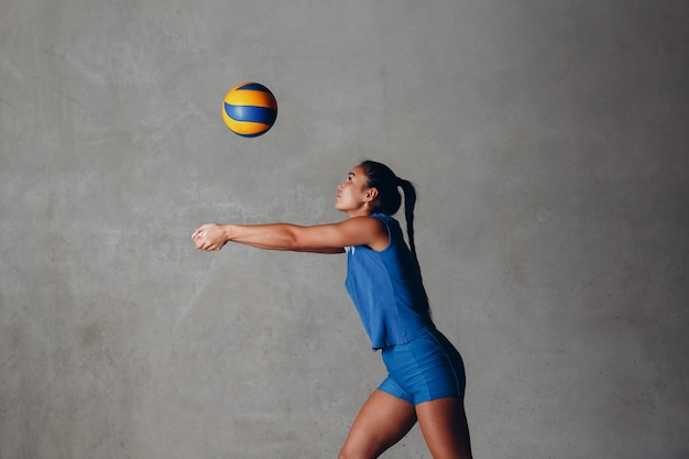 Giovane giocatore di pallavolo asiatico della donna in uniforme blu con la palla