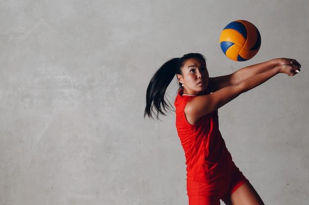 Il giovane giocatore di pallavolo asiatico della donna in uniforme rossa prende la palla