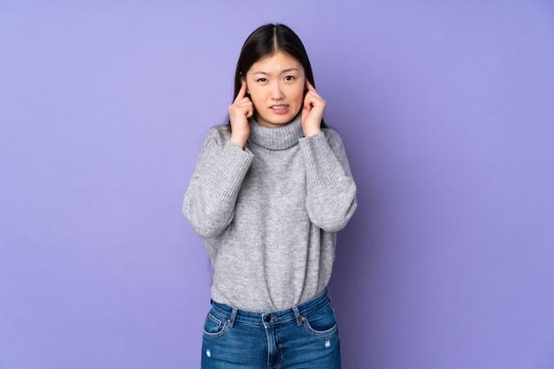 Giovane donna asiatica sopra la parete frustrata e che copre le orecchie
