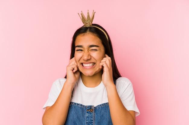 Giovane donna asiatica che indossa una corona che copre le orecchie con le mani.