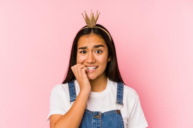 La giovane donna asiatica che indossa una corona ha isolato le unghie mordaci, nervose e molto ansiose.