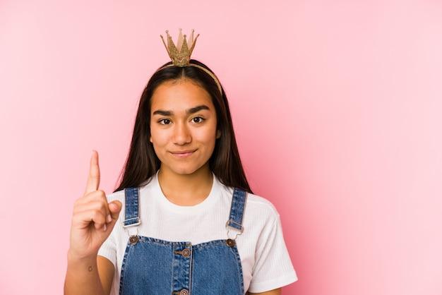 La giovane donna asiatica che indossa una corona ha isolato la mostra del numero uno con il dito.