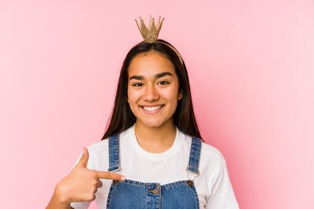 Giovane donna asiatica che indossa una persona della corona che indica a mano uno spazio della camicia, fiero e sicuro