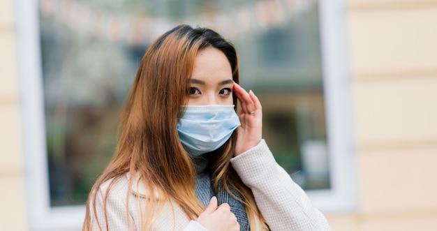 La giovane donna asiatica che indossa la maschera per il viso è in piedi in una strada domestica. nuova epidemia normale di covid-19