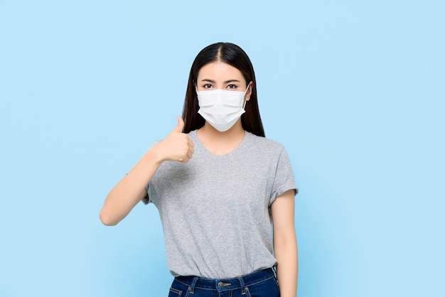 Maschera facciale d'uso della giovane donna asiatica che protegge coronavirus e le allergie che danno i pollici su isolati sulla parete blu-chiaro