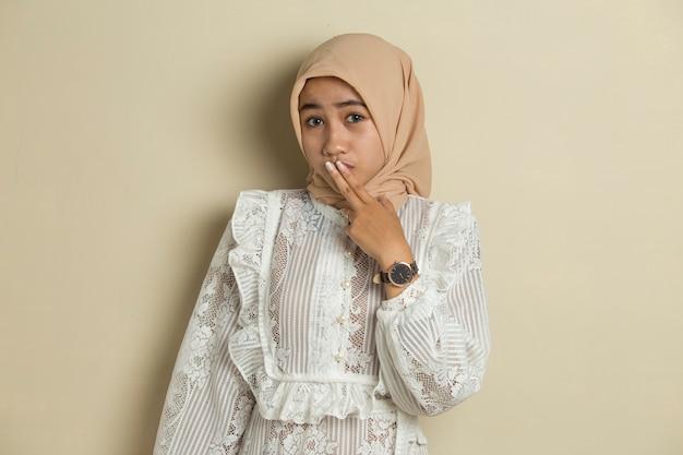 Giovane donna asiatica che indossa l'hijab scioccato che copre la bocca con le mani per errore. concetto segreto.