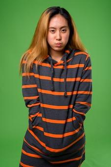 Giovane donna asiatica che indossa felpa con cappuccio contro lo spazio verde