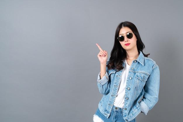 Giovane donna asiatica che indossa jeans giacca e occhiali da sole con copia spazio
