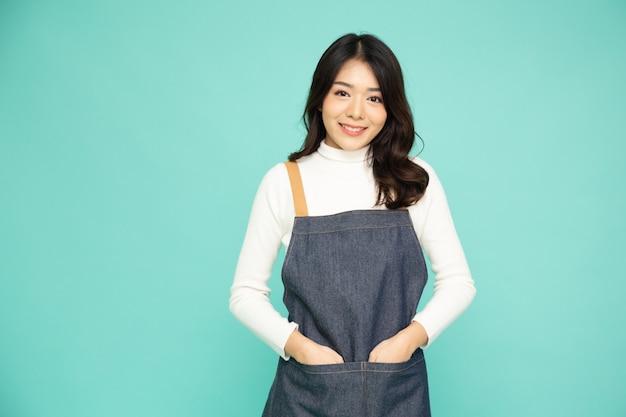 Giovane donna asiatica che indossa jeans grembiule in piedi isolato su sfondo verde