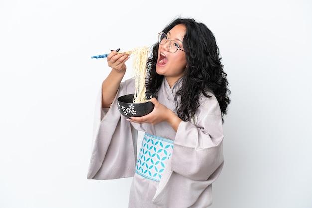 Giovane donna asiatica che indossa un kimono isolato su sfondo bianco che tiene una ciotola di pasta con le bacchette e la mangia