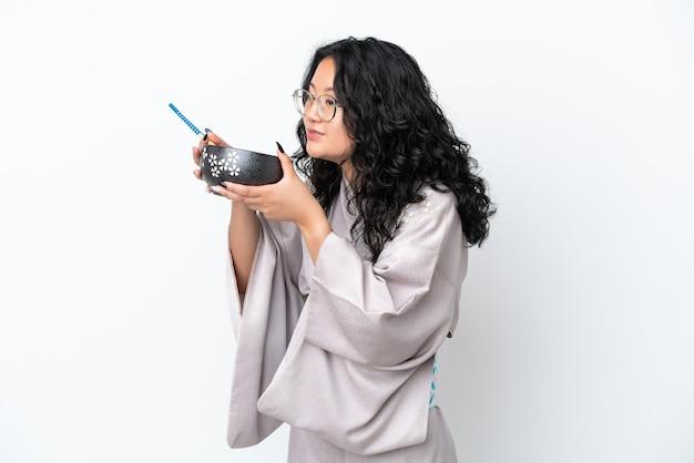 Giovane donna asiatica che indossa il kimono isolato su sfondo bianco tenendo una ciotola di noodles con i bastoncini