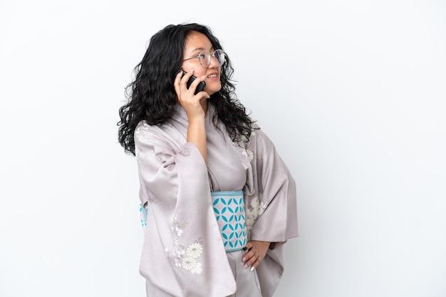 Giovane donna asiatica che indossa un kimono isolato su sfondo bianco mantenendo una conversazione con il telefono cellulare con qualcuno