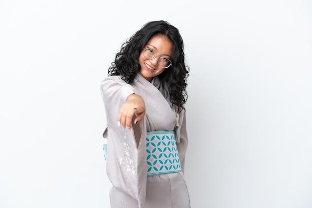 La giovane donna asiatica che indossa il kimono isolato su sfondo bianco punta il dito contro di te con un'espressione sicura