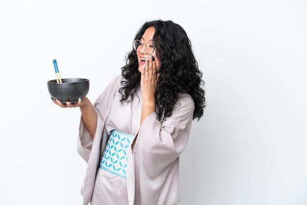 Giovane donna asiatica che indossa un kimono isolato su sfondo bianco con espressione facciale sorpresa e scioccata mentre tiene in mano una ciotola di noodles con le bacchette