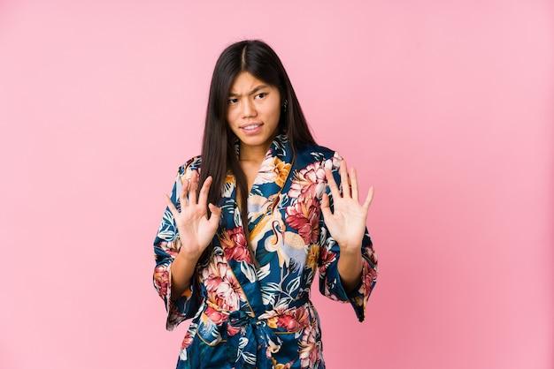 Giovane donna asiatica che indossa un pigiama kimono che rifiuta qualcuno che mostra un gesto di disgusto.