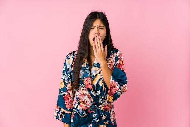 Giovane donna asiatica che indossa un pigiama kimono che sbadiglia mostrando un gesto stanco che copre la bocca con la mano.
