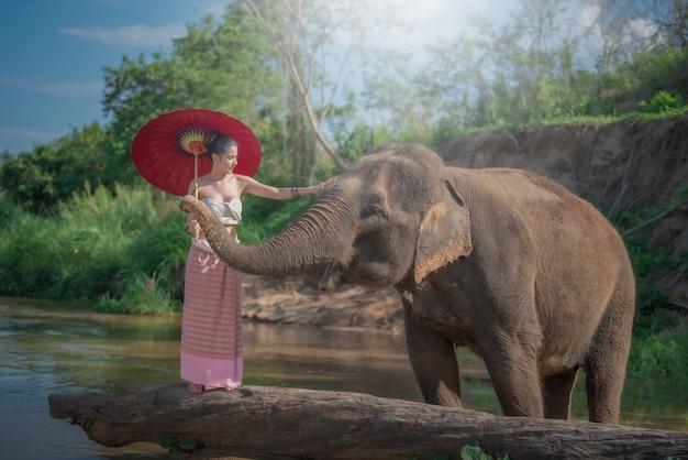 Giovane donna asiatica che indossa lanna in stile tradizionale costume con elefante a chiang mai, thailandia.