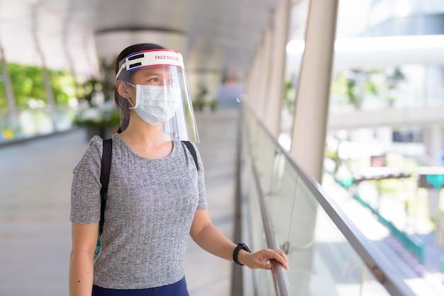 Giovane donna asiatica che indossa una maschera e una protezione per il viso per la protezione dallo scoppio del virus corona in città
