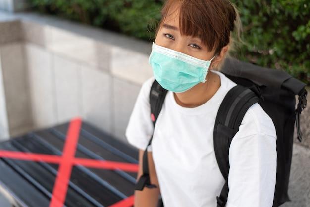 Giovane donna asiatica che indossa una maschera per prevenire il coronavirus, si siede su una sedia con il simbolo rosso distanziamento sociale, concetto covid-19