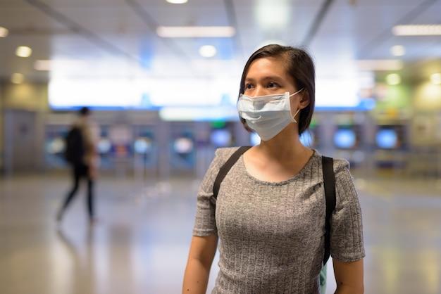 Giovane donna asiatica che indossa una maschera per proteggersi dall'epidemia di coronavirus alla stazione della metropolitana