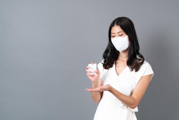 Giovane donna asiatica che indossa la maschera e utilizza uno spray alcolico a portata di mano per proteggere il coronavirus su grigio