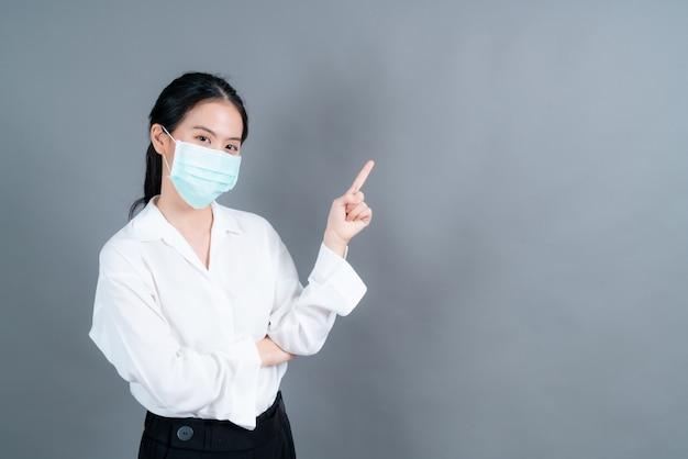 Giovane donna asiatica che indossa maschera facciale medica e dito puntato sullo spazio della copia