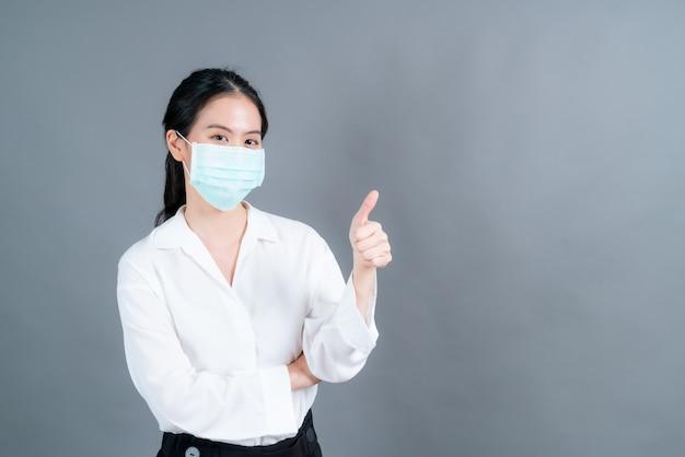 Giovane donna asiatica che indossa una maschera medica per proteggere la polvere del filtro pm2.5 anti-inquinamento, anti-smog, covid-19 e dando pollice in alto