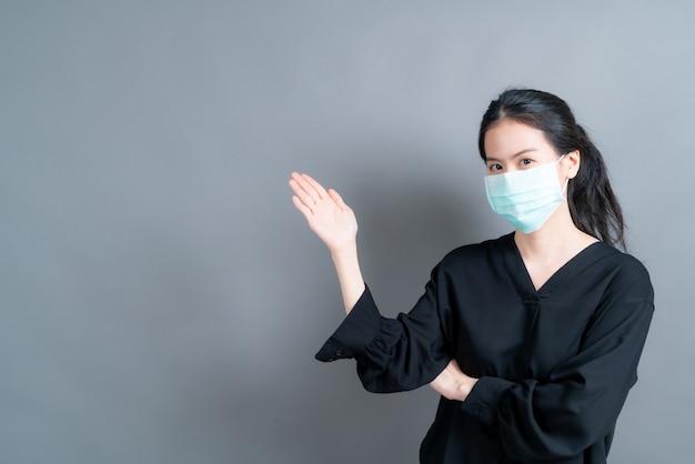 Giovane donna asiatica che indossa una maschera medica per proteggere la polvere del filtro pm2.5 anti-inquinamento, anti-smog e covid-19 con la mano che presenta sul lato
