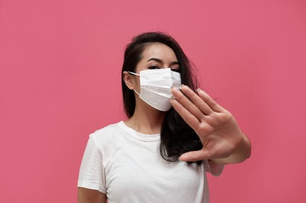Giovane donna asiatica che indossa maschera protettiva o maschera chirurgica per virus protetti e inquinamento atmosferico che fa fermare il virus a mano sul muro rosa, assistenza sanitaria e concetto di coronavirus