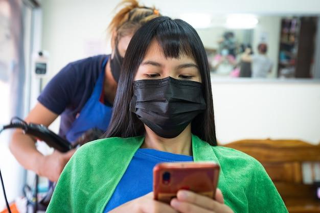Giovane donna asiatica che indossa una maschera di protezione e usa lo smartphone mentre si asciuga i capelli con l'asciugacapelli dal parrucchiere. parrucchiere che asciuga i capelli al cliente al parrucchiere.
