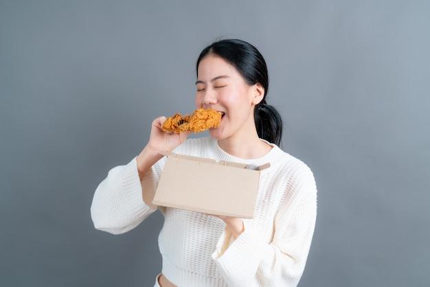 Giovane donna asiatica che indossa un maglione con la faccia felice e si diverte a mangiare pollo fritto