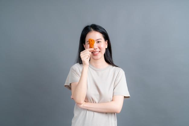 Giovane donna asiatica che indossa la maglietta con la faccia felice e piace mangiare pollo fritto sul muro grigio