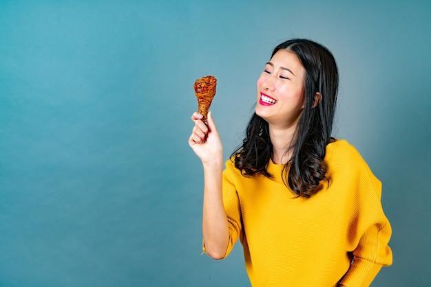 Giovane donna asiatica che indossa una camicia gialla con la faccia felice e piace mangiare coscia di pollo fritto sulla parete blu