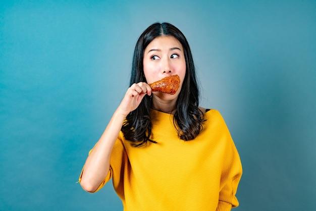 La giovane donna asiatica che porta la camicia gialla con la faccia felice e gode di mangiare la coscia di pollo fritto sull'azzurro