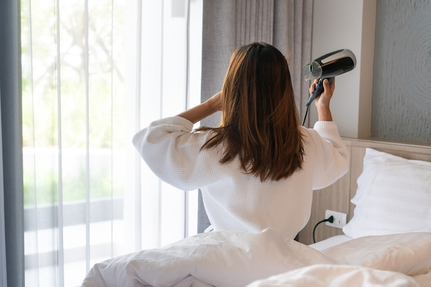 Giovane donna asiatica in accappatoio bianco seduto sul suo letto e asciugare i capelli al mattino