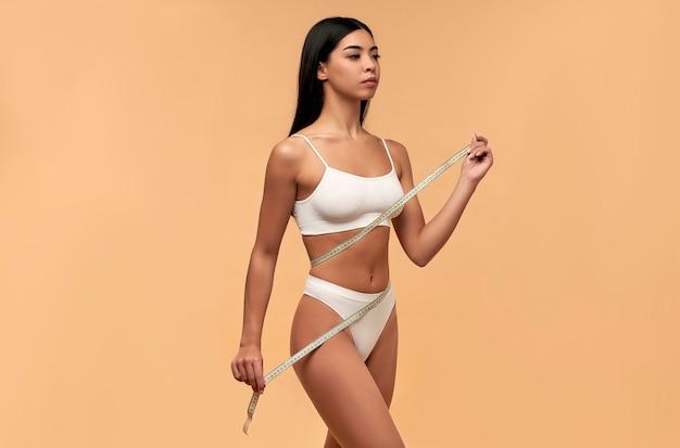 Giovane donna asiatica in lingerie bianca con un corpo tonico e una figura snella con un metro a nastro sul beige. sport, stile di vita sano