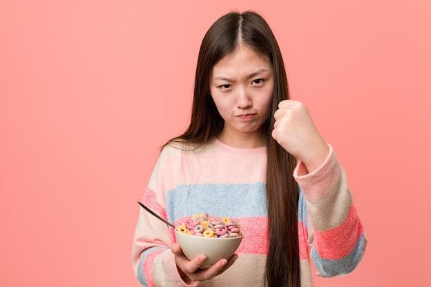 Giovane donna asiatica con una ciotola di cereali che mostra il pugno alla telecamera, espressione facciale aggressiva.