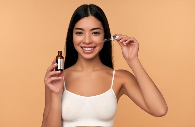 La giovane donna asiatica con la pelle pulita e radiosa in lingerie bianca utilizza un siero idratante su una parete beige.