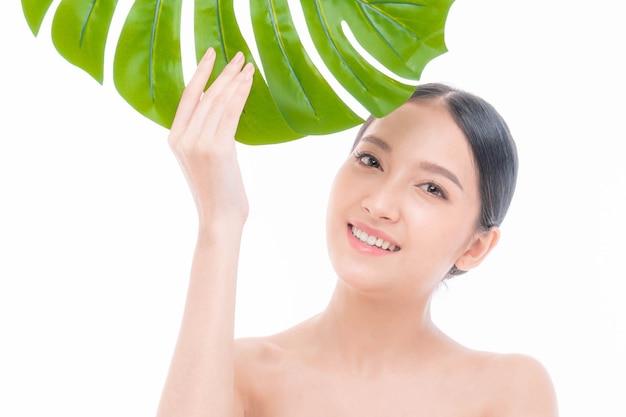 Giovane donna asiatica con pelle pulita, pelle fresca che tiene in mano una foglia tropicale verde