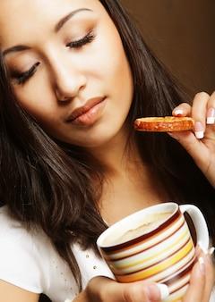 Giovane donna asiatica con caffè e biscotti.