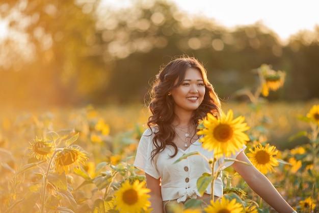 Giovane donna asiatica con capelli ricci in un campo di girasoli al tramonto.