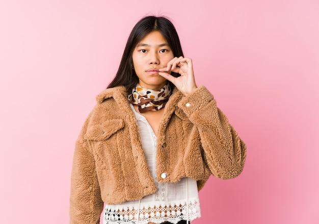 Giovane donna asiatica con le dita sulle labbra mantenendo un segreto.