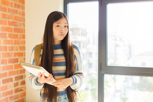 Giovane donna asiatica con un'espressione sciocca, pazza, sorpresa, guance gonfie, sentirsi imbottita, grassa e piena di cibo
